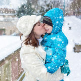 Little toddler kid boy and mother having fun with snow on winter day Royalty Free Stock Images