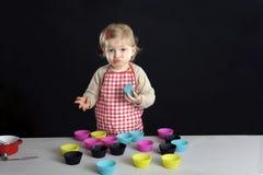 Little toddler making cupcakes, royalty free stock image