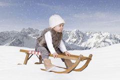 Little toddler outdoors in the snow in the alps Stock Images