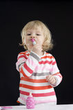 Little toddler plaing with make-up toys on black Royalty Free Stock Photo