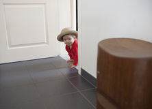 Little toddler playing hide and seek. Inside Royalty Free Stock Image