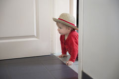 Little toddler playing hide and seek. Inside Stock Photo