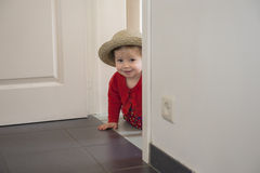 Little toddler playing hide and seek. Inside Stock Images