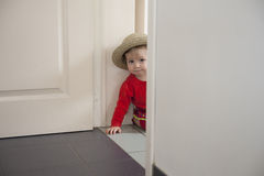 Little toddler playing hide and seek Stock Photo