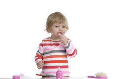 Little toddler playing with make-up toys on Stock Image