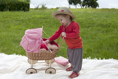 Little toddler playing with a pram outdoors Stock Photography
