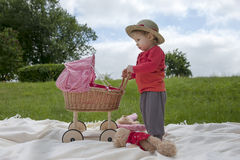 Little toddler playing with a pram outdoors Royalty Free Stock Image