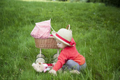 Little toddler playing with a pram outdoors Stock Photo