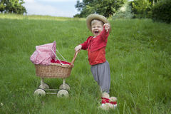 Little toddler playing with a pram outdoors Royalty Free Stock Photos