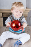 Little toddler playing with red Christmas tree ball Royalty Free Stock Photography