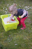 Little toddler playing with sand in the garden Stock Photography