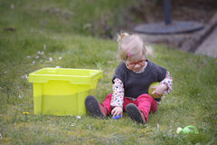 Little toddler playing with sand in the garden Royalty Free Stock Image