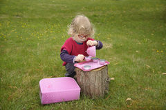 Little toddler playing Tea time outdoors in the garden Stock Image