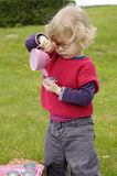 Little toddler playing  tea time outdoors in the garden Royalty Free Stock Photography