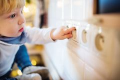 Toddler boy in dangerous situation at home. Child safety concept. Little toddler putting fingers in a power socket. Domestic accident. Dangerous situation at royalty free stock photos