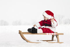 Little toddler in santa claus outfit in the snow Royalty Free Stock Photos