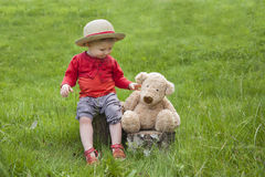 Little toddler seated in the garden with her teddy Royalty Free Stock Images