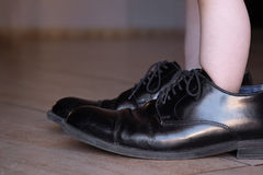 Little Toddler Stepping in Daddy`s Big Fancy Shoes Royalty Free Stock Photos