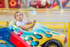 Little toddler in theme park: a boy in white shirt riding little car on merry go round, bright amusements in background stock photo