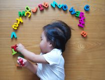 Little toddler top down view with her toys. Little toddler top down view with her alphabet toys Stock Images