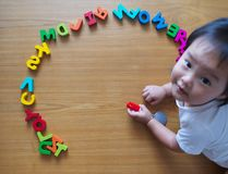 Little toddler top down view with her toys. Little toddler top down view with her alphabet toys Royalty Free Stock Photo