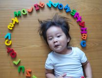 Little toddler top down view with her toys. Little toddler top down view with her alphabet toys Royalty Free Stock Images