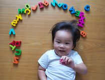 Little toddler top down view with her toys. Little toddler top down view with her alphabet toys Stock Photo