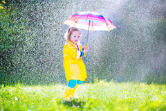 Little toddler with umbrella playing in the rain Stock Image