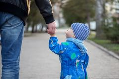 Little toddler on a walk with father, holding dad`s hand a having turned to him, asking something stock photography