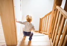 Toddler boy in dangerous situation at home. Child safety concept. Little toddler walking down the stairs. Domestic accident. Dangerous situation at home. Child Royalty Free Stock Images