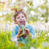 Little toddler wearing Easter bunny ears and eating chocolate at stock images