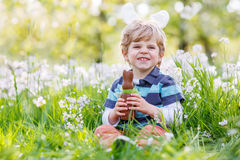 Little toddler wearing Easter bunny ears and eating chocolate at Royalty Free Stock Photo