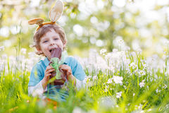 Little toddler wearing Easter bunny ears and eating chocolate at Royalty Free Stock Images