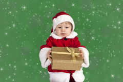 Little toddler in xmas outfit giving a present Royalty Free Stock Images