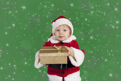 Little toddler in xmas outfit giving a present Stock Photos