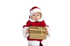 Little toddler in xmas outfit giving a present Royalty Free Stock Photo
