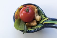Little tomato with some cashew nuts, basil and rosemaries on a b. High-angle shot. Seen from above. Close-up stock image