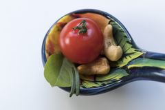 Little tomato with some cashew nuts, basil and rosemaries on a b. High-angle shot. Seen from above. Close-up Royalty Free Stock Image