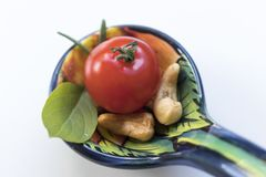 Little tomato with some cashew nuts, basil and rosemaries on a b. High-angle shot. Seen from above. Close-up Royalty Free Stock Photo
