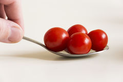 Little tomatoes on a spoon. Little red tomatoes on a spoon with white background Stock Image