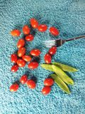 Little tomatos and fork. View of baby plum tomatos,mange tout and fork Royalty Free Stock Photos