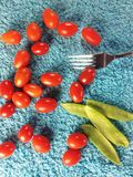 Little tomatos and fork. View of baby plum tomatos,mange tout and fork Royalty Free Stock Images
