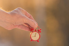 Little too late. Hand holding a alarm clock with the time pas twelve Stock Image