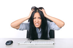 A little too stressed. A stressed out young girl grabbing her hair while sitting at a desk with a keyboard and mouse Stock Image