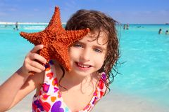 Little tourist girl holding starfish beach Stock Photography