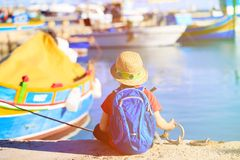 Little tourist looking at traditional boats in Stock Image