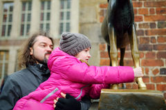 Little tourist touching famous statue in the center of Bremen known as Bremen Town Musicians. Which supposed to bring good luck royalty free stock photography