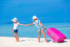 Little tourists girls with big suitcase on tropical white beach. Travel concept. Royalty Free Stock Image
