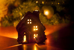 Little toy Christmas house with a burning light inside is on the table near the Christmas tree.  royalty free stock image