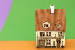 Little toy house on orange green backgrounds. Little toy house on orange green and violet backgrounds royalty free stock image